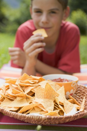 10 to 12 year olds: Boy eating nachos with salsa in garden LANG_EVOIMAGES