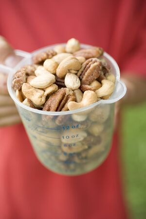 mixed nuts: Person holding measuring jug full of mixed nuts