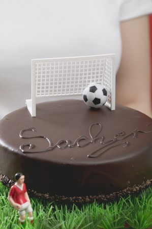 coatings: Woman holding Sacher torte with football figure & football