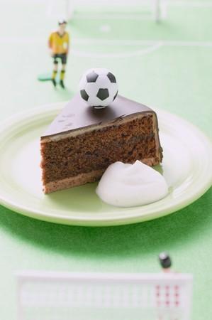 cuisines: Piece of Sacher torte with cream, football & football figure