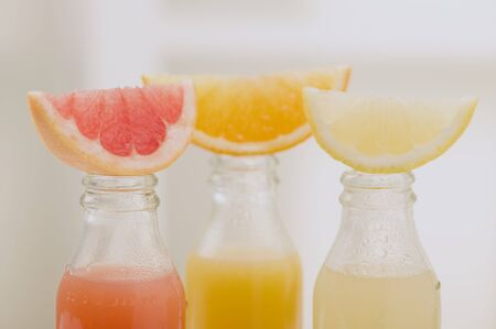 soda pops: Three fruit juices in bottles with wedges of fresh fruit