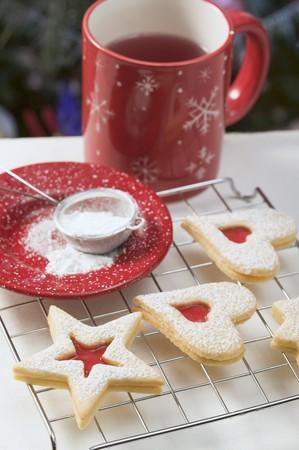 jam biscuits: Biscotti di marmellata sulla torta rack, zucchero a velo, tazza di t� LANG_EVOIMAGES