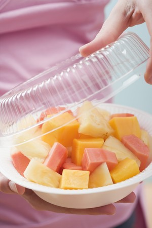well beings: Woman removing lid from plastic dish of exotic fruit salad