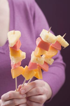 well beings: Woman holding three exotic fruit skewers LANG_EVOIMAGES