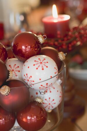 ignited: Assorted Christmas tree baubles in front of red candle LANG_EVOIMAGES