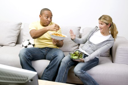 Couple with peanut puffs and salad in front of TV
