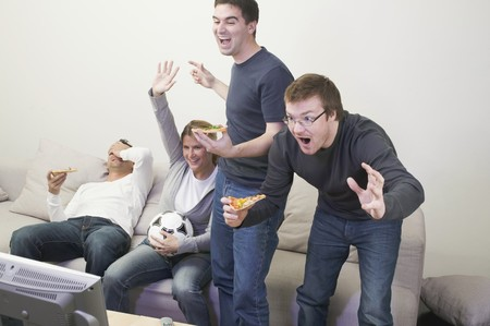 four year olds: Cheering friends in front of TV with pizza and football LANG_EVOIMAGES
