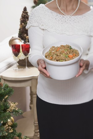 stuffing: Woman holding large dish of bread stuffing (Christmas) LANG_EVOIMAGES