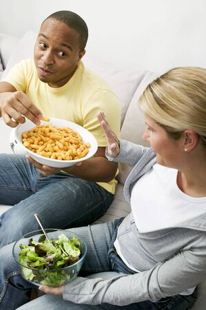 nibble: Couple on sofa with peanut puffs and salad