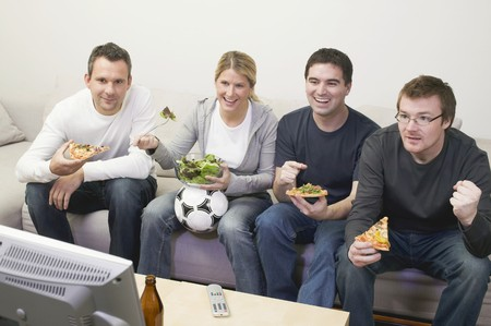 20 to 25 year olds: Friends in front of TV with pizza, salad and football LANG_EVOIMAGES