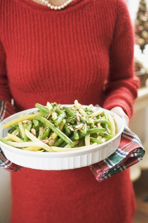 yellowish green: Woman holding dish of beans with flaked almonds (Christmas)