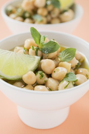 chickpeas: Chick-peas with lime wedges and herbs (close-up)