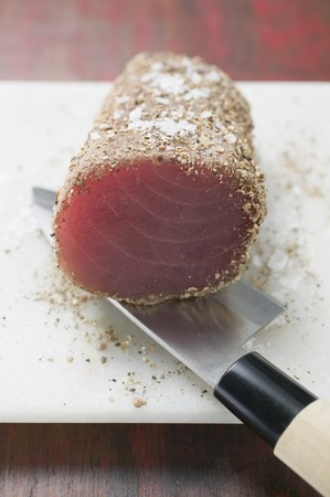 tunafish: Raw tuna fillet with salt and pepper on knife