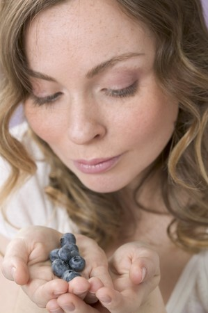 20 to 25 year olds: Woman holding fresh blueberries