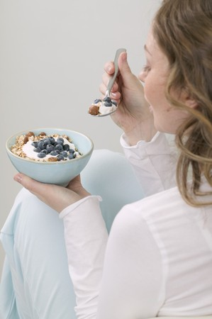 roughage: Woman eating muesli with blueberries