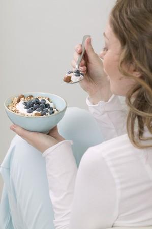 well beings: Woman eating muesli with blueberries