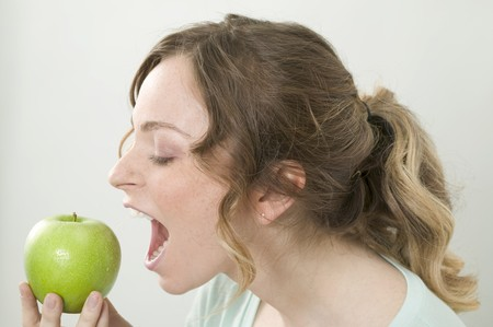 well beings: Woman biting into green apple LANG_EVOIMAGES