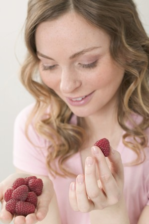 20 to 25 year olds: Woman holding fresh raspberries