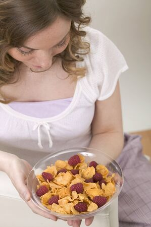 20 to 25 year olds: Woman holding bowl of cornflakes with raspberries LANG_EVOIMAGES
