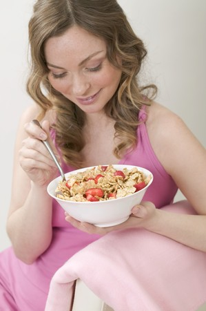 roughage: Woman eating cornflakes with strawberries