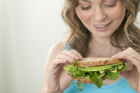 water cress: Woman holding wholemeal avocado and watercress sandwich