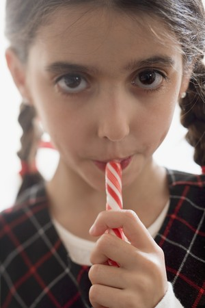 candy stick: Girl eating candy stick LANG_EVOIMAGES