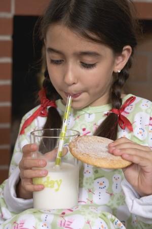 tomando leche: Muchacha que bebe la leche y la celebraci�n de la galleta