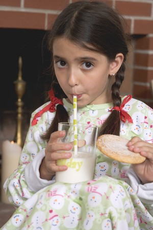 nightdress: Girl drinking milk and holding biscuit LANG_EVOIMAGES