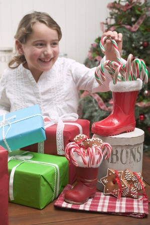 10 to 12 year olds: Girl reaching for candy cane LANG_EVOIMAGES