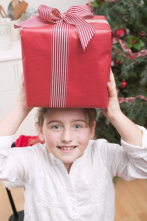 10 to 12 year olds: Girl balancing Christmas gift on her head
