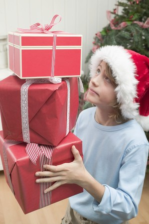 10 to 12 year olds: Boy in Father Christmas hat carrying pile of parcels