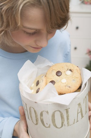 10 to 12 year olds: Boy looking at chocolate chip cookies in cookie tin LANG_EVOIMAGES