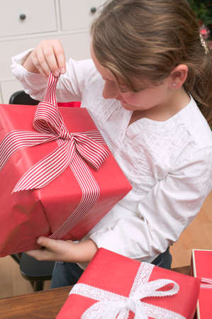 10 to 12 year olds: Girl opening Christmas parcel