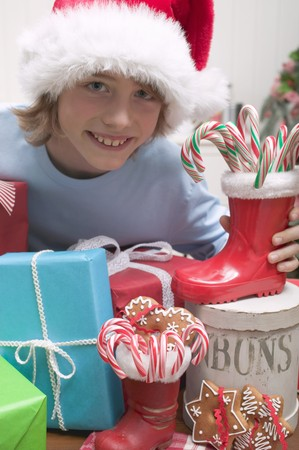 10 to 12 year olds: Boy in Father Christmas hat with gifts LANG_EVOIMAGES