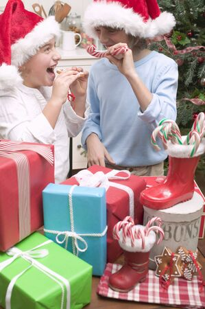 10 to 12 year olds: Girl and boy in Father Christmas hats with gifts