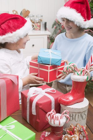 10 to 12 year olds: Girl and boy in Father Christmas hats exchanging gifts LANG_EVOIMAGES