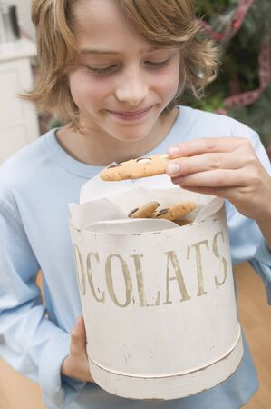 casual clothing 12 year old: Boy taking chocolate chip cookie out of cookie tin