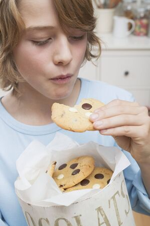 casual clothing 12 year old: Boy eating chocolate chip cookie out of cookie tin