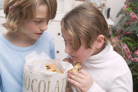 10 to 12 year olds: Boy and girl eating chocolate chip cookies