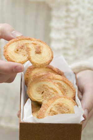 pastes: Hand taking palmier (puff pastry biscuit) from box LANG_EVOIMAGES