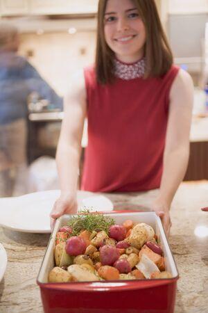 root vegetables: Giovane donna che tiene ortaggi a radice arrostito in torrefazione piatto
