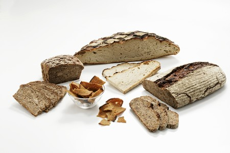 several breads: Loaves of wood-oven bread, partly sliced, & toasted bread