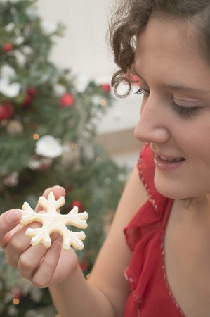 25 to 30 year olds: Woman holding Christmas biscuit