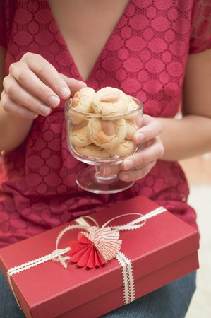 almond biscuit: Woman reaching for almond biscuit in glass LANG_EVOIMAGES
