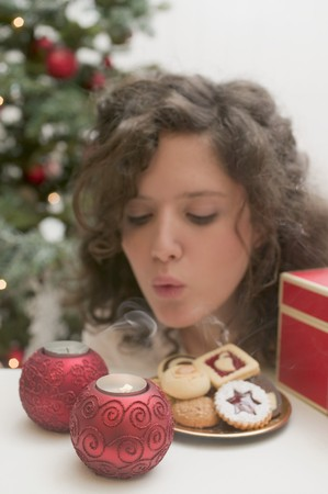 blowing out: Woman blowing out tealights (Christmas)
