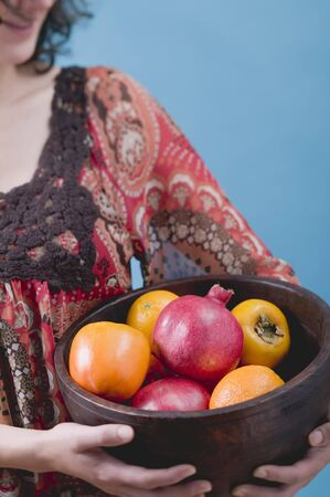 25 to 30 year olds: Woman holding fresh fruit in wooden bowl