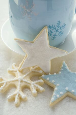 star shaped: Three iced Christmas biscuits in front of blue cup