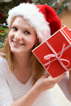 25 to 30 year olds: Woman in Father Christmas hat holding Christmas gift LANG_EVOIMAGES