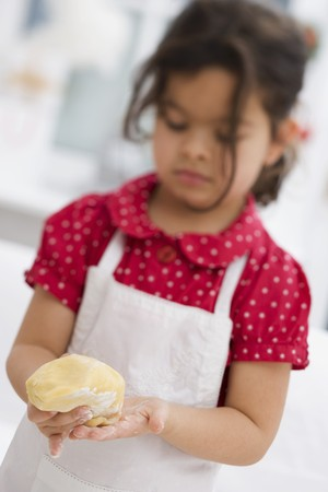 solo form: Small girl forming dough into a ball