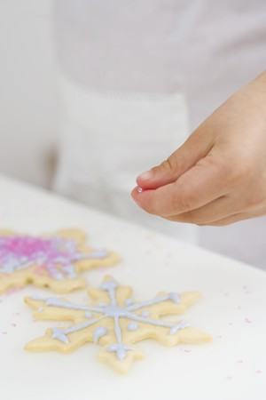 dragee: Child decorating Christmas biscuit with silver balls